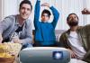 Drei Männer auf der Couch schauen fern mit BenQ Beamer. Foto: BenQ