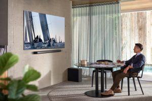 Samsung Q950T QLED 8K mit Soundbar Mann sitzt in Raum vor Fernseher
