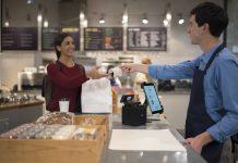 Mann gibt Rechnung aus Epson-Kassensystem über den Tresen an Frau. Foto: Epson