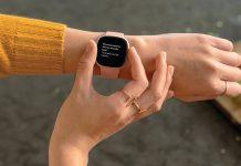 Fitbit Versa 3: Frau zeigt Smartwatch am Handgelenk