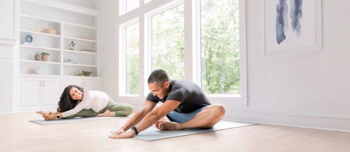 Mann und Frau beim Yoga im Wohnzimmer mit Garmin-Smartwatch Venu Sq