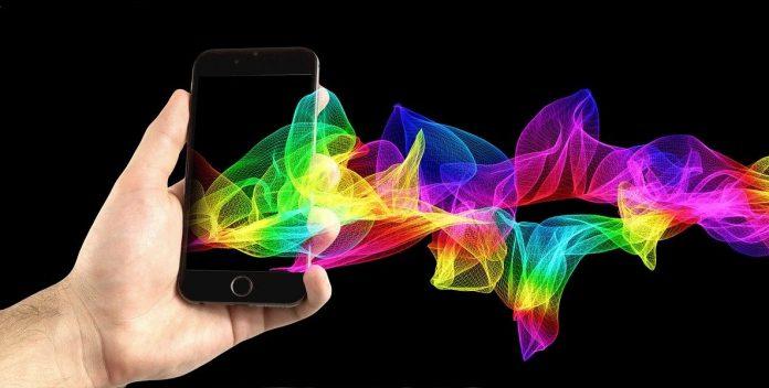 Smartphone in der Hand mit buntem Streifen