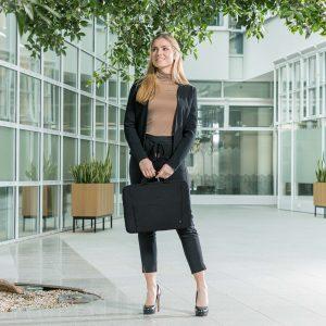 Elegante Business-Frau mit Dicota Notebook-Tasche Eco Slim Case Base in der Hand