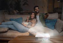 BenQ W1800i - Paar sitzt auf Sofa und schaut auf Heimkino-Projektor