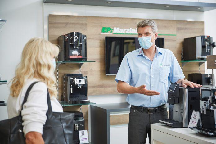 Fachhändler von EP:Marzini im Kundengespräch, Händler mit Covid-Maske steht im ElectronicPartner Ladengeschäft