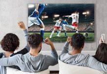 Fußball auf dem Grundig-Fernseher GOB 9099 Fire TV, Menschen jubeln auf dem Sofa vor dem TV-Gerät