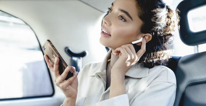 Panasonic-Ohrhörer-RZ-B100W in Weiß - Frau im Auto hört Sound per Smartphone