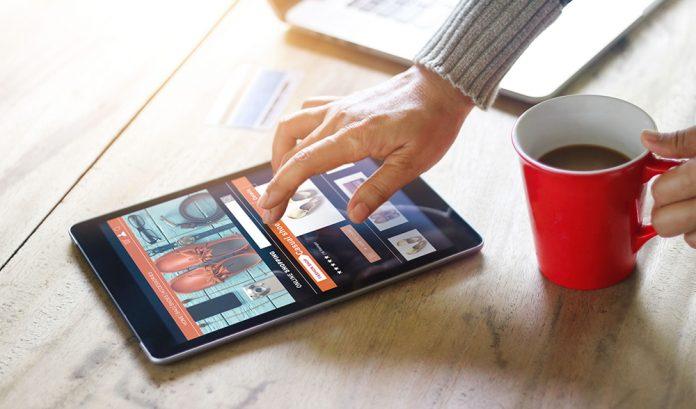 Online-Shopping - Mensch tippt auf Tablet und hält eine Kaffeetasse