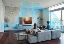 HT-A7000 Soundbar von Sony - Klangwellen im Raum, Familie sitzt auf Sofa und lauscht dem Heimkino-Sound