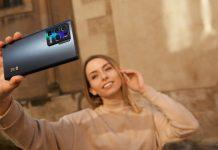 Hübsche Frau macht Selfie mit Axon 30 Smartphone von ZTE vor steinerner Häuserwand