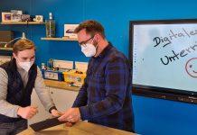 zwei junge Menschen mit Covid-Maske vor interaktiver Tafel, digitale Schule