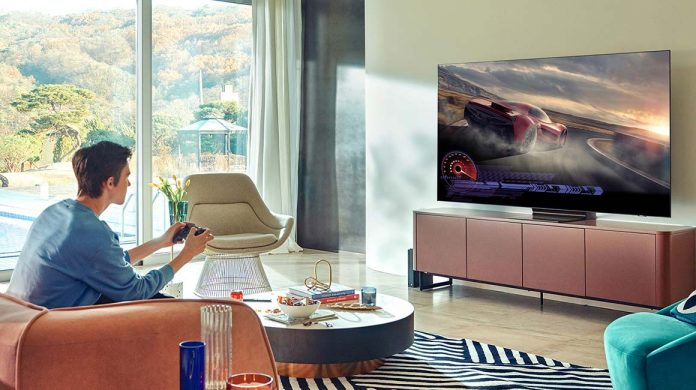 Samsung QN95A TV im Wohnzimmer - Mann auf Sofa sitzt vor Fernseher