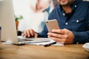 Mann mit Smartphone in der Hand vor dem Notebook - Später Bezahlen Angebote von PayPal