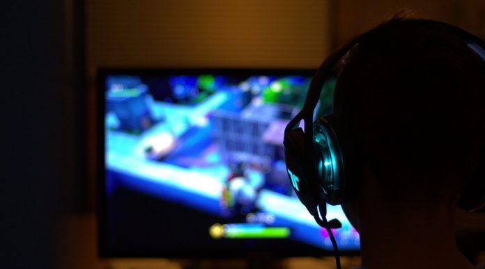 Gamer vorm Bildschirm spielt Fortnite