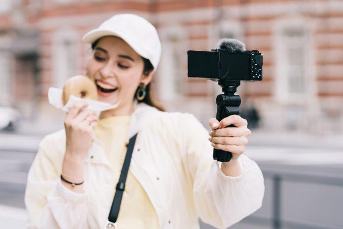 ZV-E10 von Sony - Frau hält Systemkamera in der Hand