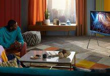 Mann und Frau sitzen auf Sofa in buntem Wohnzimmer und schauen Fernsehen auf Samsung The Serif