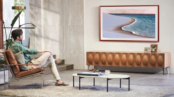 Mann sitzt auf Stuhl im Wohnzimmer und schaut Fernsehen auf Samsung The Frame