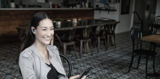 Frau im Cafe mit Shure Ohrhörer Aonic 215