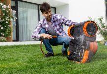 Mann im Garten mit Rasenmähroboter Navimow
