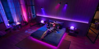 Philips Hue und Spotify - Mann liegt auf Bett und hört Musik mit dazu vernetztem Licht