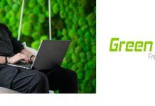 Bärtiger Mann tippt auf Notebook vor grüner Wand - Green Cell