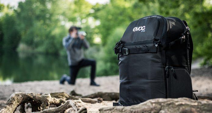Fotograf im Grünen mit Evoc-Rucksack im Vordergrund