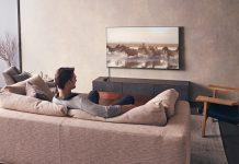 Nackenbügel-Lautsprecher SRS-NS7 von Sony - Mann sitzt auf Couch vor Fernseher